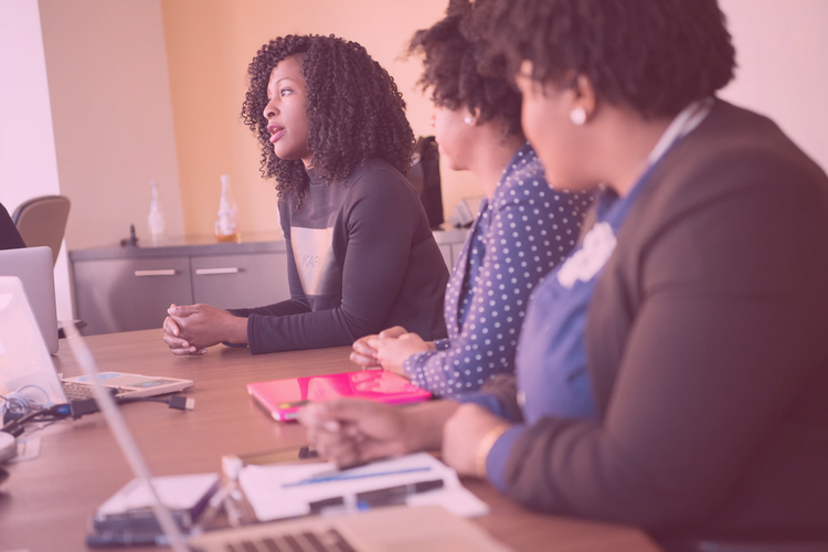 women of colour discussing around a conference table office