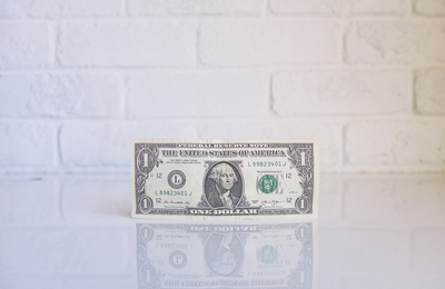one dollar bill on white surface in front of white brick wall