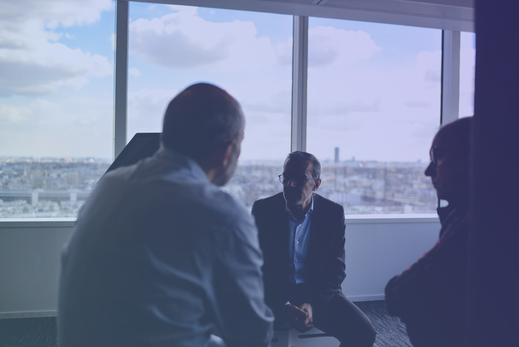 businessman in room talking to colleagues in front of big window with city view