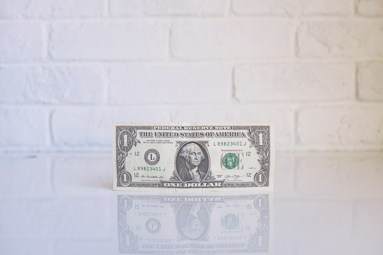 money in front of brick wall